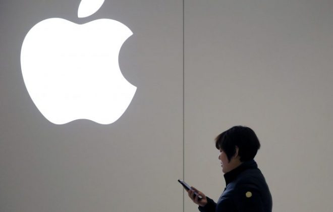 A Chinese woman uses her mobile phone as she walks past an Apple logo outside an Apple Store in Beijing, China, 04 January 2019.